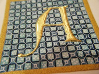 Raised guilded letter A with gouache and watercolour diaper detail. Shell gold border.